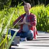 Man practising yoga sitting on wood bridge with reed around Stock Photo