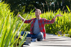 Man practising yoga sitting on wood bridge with water grass Stock Photo