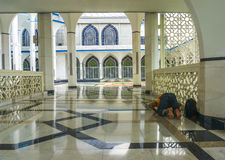 Man pray. A man pray at mosque corridor with shine floor marbe Royalty Free Stock Photos