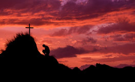 Man In Prayer. Man below a cross on a hill, praying as the sunsets stock photo