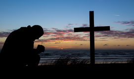 Man Of Prayer. Man praying by a cross at the beach while the sunset for another day Royalty Free Stock Photography