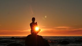 Man prayer and worship to sun in the island in sea dolly shot stock video