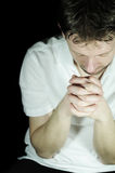 Man praying. Portrait of a young man praying in the dark Royalty Free Stock Photography
