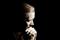Man praying. Head and hands of praying man, low-key portrait royalty free stock image