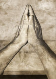 Man praying. Sepia image of the hands of a man, put on a wooden support, in an attitude of prayer Royalty Free Stock Image