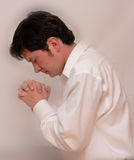 Man Praying. With hands folded on white background for easy removal or addition of text Stock Photos