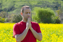 Man praying alone in a an open field in nature. Royalty Free Stock Photos