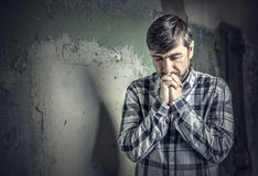 Man praying. On the background of old wall Stock Images