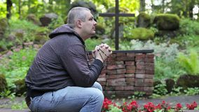 Man praying on bench with the rosary at outdoors church stock video