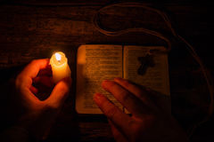 Man praying on the Bible in the light candles Royalty Free Stock Photos