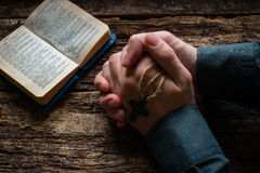 Man praying before a bible on table Stock Images