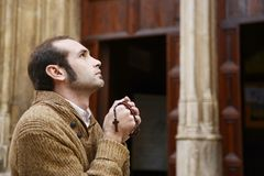Man praying in church holding prayer beads. Man or monk praying in front of the church with rosario or prayer beads royalty free stock photos