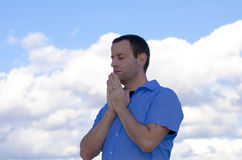 Man praying in the clouds. Royalty Free Stock Images