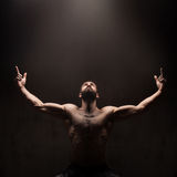 Man praying on dark studio background Royalty Free Stock Image