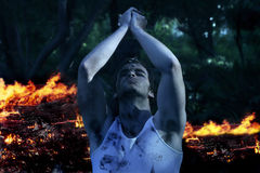 Man Praying with fire in background stock image