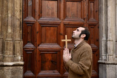Man praying in front of the church holding a cross Stock Photography
