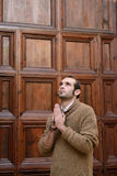 Man praying in front of the church holding prayer beads Royalty Free Stock Photography