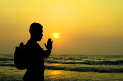 A man praying in front of a golden sunrise on the beach Royalty Free Stock Photography
