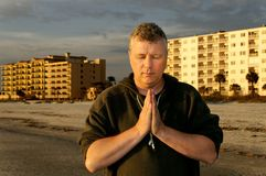 Man Praying in Front of Hotels Royalty Free Stock Image