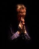 A man praying. A front view of a man praying in the dark with a ray of sunlight shining down on him royalty free stock photos