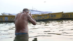 Man praying in Ganges river in Varanasi at sunset. VARANASI, INDIA - 22 FEBRUARY 2015: Man praying in Ganges river in Varanasi at sunset stock footage