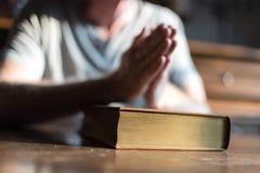 Man praying hands on a Bible. Man sitting at a table praying hands on a Bible stock photos