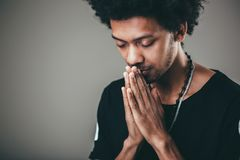 Man praying hands clasped hoping for best asking for forgiveness or miracle. Praying african american man hoping for better. Asking God for good luck, success Royalty Free Stock Image