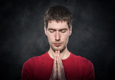 Man praying with hands clasped. Man praying with hands clasped over dark background Royalty Free Stock Images