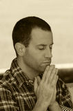 Man praying with hands together in sepia tone. Royalty Free Stock Images