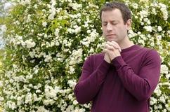 Man praying with his hands interlocked. Stock Image