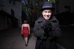Man praying on his next victim. Man wearing a coat and hat praying on his next female victim Royalty Free Stock Image