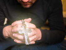 Man praying and holding a cross with Jesus Stock Photo