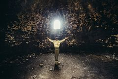 Man praying and hoping with arms raised up to the mystery light. Religion miracle concept.  Stock Images