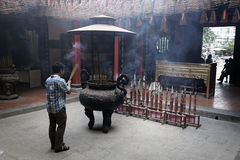 Man praying in incense smoke filled temple in Ho Chi Minh City Royalty Free Stock Images