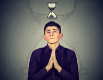 Man praying looking up at sand clock pressured by lack of time Stock Photo