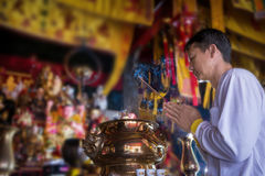 Man praying for new year ,Lighting incense to Buddha. NBurning joss stick and oil palm candle at chinese shrine for making merit in chinese new year festival Royalty Free Stock Image