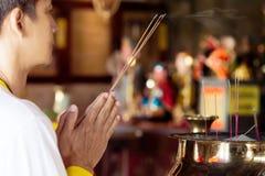Man praying for new year ,lighting incense to Buddha. Royalty Free Stock Image