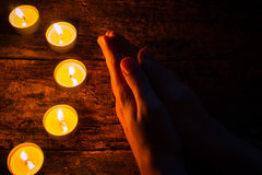 Man praying next to the candles on wooden table Stock Images