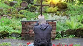 Man praying in outdoors church opposite the cross. In summer day