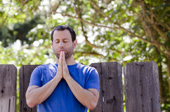 Man praying outside in front of a wooden fence. Royalty Free Stock Photos