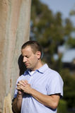 Man praying outside. Man praying with hands folded outside leaning on tree Royalty Free Stock Photography