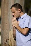 Man praying outside. Man praying outside leaning on tree Stock Image