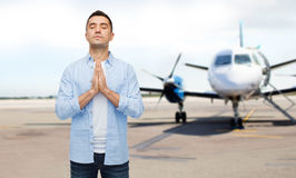 Man praying over airplane on runway background. Faith in god, hope and people concept - happy man with closed eyes praying over airplane on runway background Royalty Free Stock Photography
