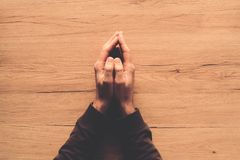 Man praying, overhead view. Of male hands on wooden church prayer kneeler stock images
