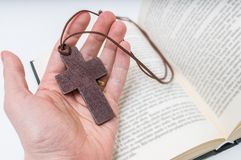 Man is praying. Prayer's hand holds crucifix. Bible in background.  Royalty Free Stock Photography