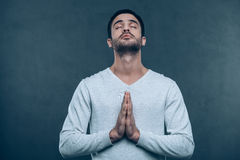 Man praying. Studio shot of handsome young man praying while holding hands clasped and keeping eyes closed stock photography