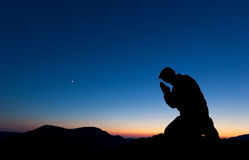 Man Praying. On the summit of a mountain at sunset with the moon in the sky Stock Photos