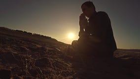 Man praying sunset god sitting silhouette sun sunlight the religion stock video