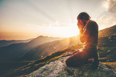 Man praying at sunset mountains Royalty Free Stock Image