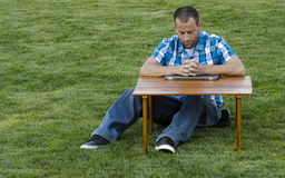 Man praying at a table with hands clasped. Man sitting and praying at a table outside on the grass with his hands clasped and head down wearing a plaid shirt Royalty Free Stock Images